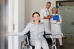 Patient in wheelchair, doctors in discussing background