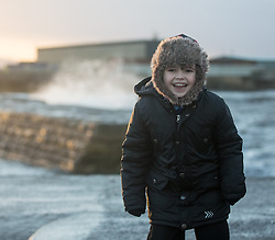 Stormy weather in East Lothian 11 January 2017; a child stands up against the wind whilst the waves crash on the sea wall at Cockenzie harbour, East Lothian.<br /> <br /> (c) Chris McCluskie | Edinburgh Elite media