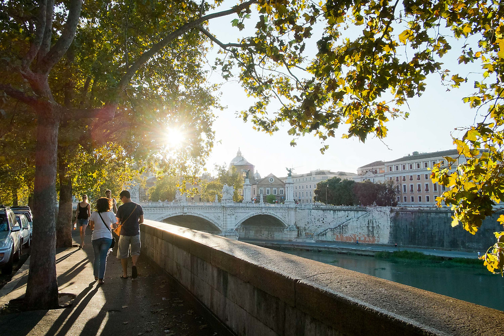 A couple walk along the river near St Angelo Castle and St Angelo Bridge, Rome, Italy.