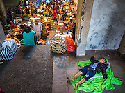 11 OCTOBER 2016 - UBUD, BALI, INDONESIA: A vendor's child sleeps in a stairwell at the morning market in Ubud. The morning market in Ubud is for produce and meat and serves local people from about 4:30 AM until about 7:30 AM. As the morning progresses the local vendors pack up and leave and vendors selling tourist curios move in. By about 8:30 AM the market is mostly a tourist market selling curios to tourists. Ubud is Bali's art and cultural center.      PHOTO BY JACK KURTZ