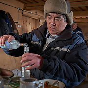 """Kim Pomishin, a shaman at a Buryati village in Selenga in the Kabansk region along the shore at Russia's Lake Baikal, uses vodka to prepare for a ritual. Crowned the """"Jewel of Siberia"""", Baikal is the world's deepest lake, and the biggest lake by volume, holding 20% of the world's fresh water. In the winter, the lake 31,722 square meter surface is entirely frozen with ice averaging 2 meters thick."""