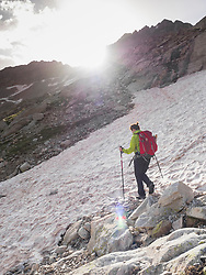 Woman hiking in the High Pyrenees crossing snow field while ascending to mount Vignemale, Cauterets, France