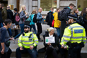 Tourists walk by as police officers arrest protesters on Whitehall on 16th October 2019 in England, United Kingdom.  Extinction Rebellion climate activists sit down in the road despite the police imposing a section 14 of the Public Order Act 1986  in effect banning all protest by the group in London.