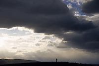 A lone mountain biker rides beneath stormy skies in Jackson Hole, Wyoming.