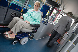 Woman sitting on bus in designated area for wheelchair users,