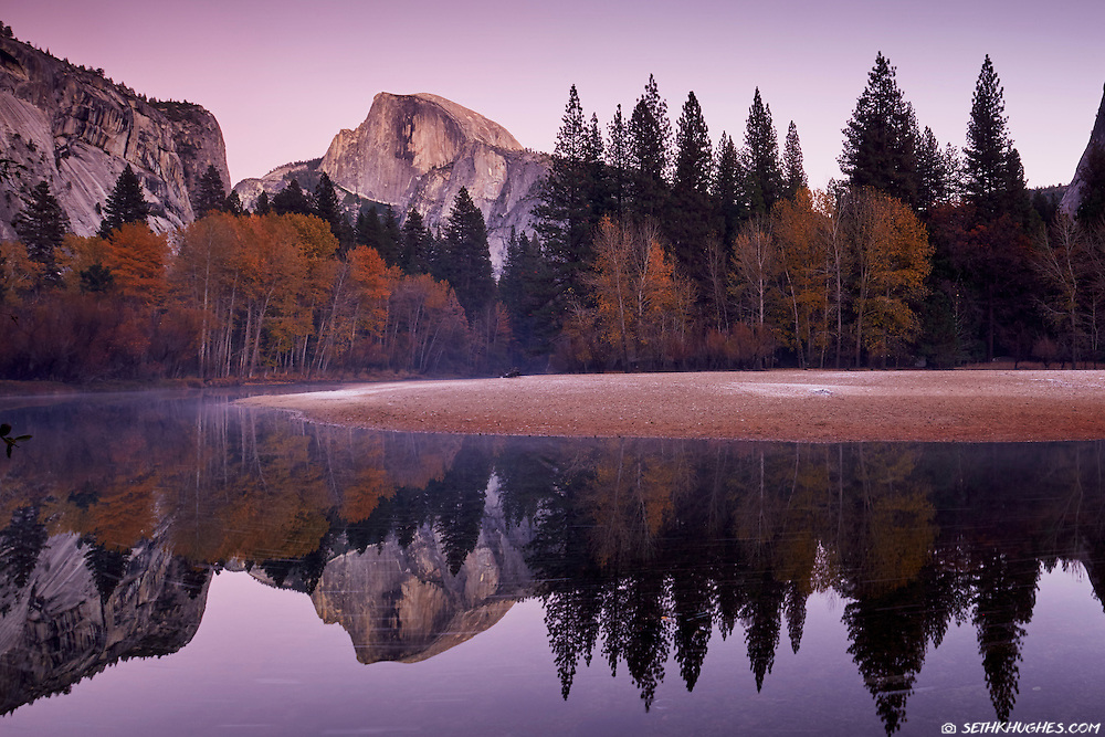 A reflective view on the Merced River of Half Dome in Yosemite National Park during twilight.