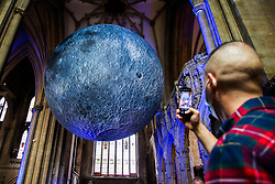 © Licensed to London News Pictures. 15/08/2021. Bristol, UK. A man takes a photograph of Luke Jeram's Moon installation in Bristol Cathedral. Measuring seven metres in diameter, the Museum of the Moon features detailed NASA imagery of the lunar surface. At an approximate scale of 1:500,000 each centimetre of the internally lit spherical sculpture represents 5 km of the moon's surface. The Museum of the Moon  is open until 30 August 2021. Photo credit: Dinendra Haria/LNP