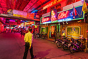 """26 SEPTEMBER 2014 - PATTAYA, CHONBURI, THAILAND: A man walks into a go-go bar near Walking Street in Pataya. Pataya, a beach resort about two hours from Bangkok, has wrestled with a reputation of having a high crime rate and being a haven for sex tourism. After the coup in May, the military government cracked down on other Thai beach resorts, notably Phuket and Hua Hin, putting military officers in charge of law enforcement and cleaning up unlicensed businesses that encroached on beaches. Pattaya city officials have launched their own crackdown and clean up in order to prevent a military crackdown. City officials have vowed to remake Pattaya as a """"family friendly"""" destination. City police and tourist police now patrol """"Walking Street,"""" Pattaya's notorious red light district, and officials are cracking down on unlicensed businesses on the beach.     PHOTO BY JACK KURTZ"""