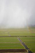 Nederland, Zuid-Holland, Krimpenerwaard, 04-03-2008; polderlandschap, ten noorden van Schoonhoven, op de grens met de Lopikerwaard; regengordijnen afgewisseld met zon, begin regenboogwei, weiland, gras, sloot; regenwolken, sluier, regensluier, wolken, noodweer, polderen, polder. .luchtfoto (toeslag); aerial photo (additional fee required); .foto Siebe Swart / photo Siebe Swart