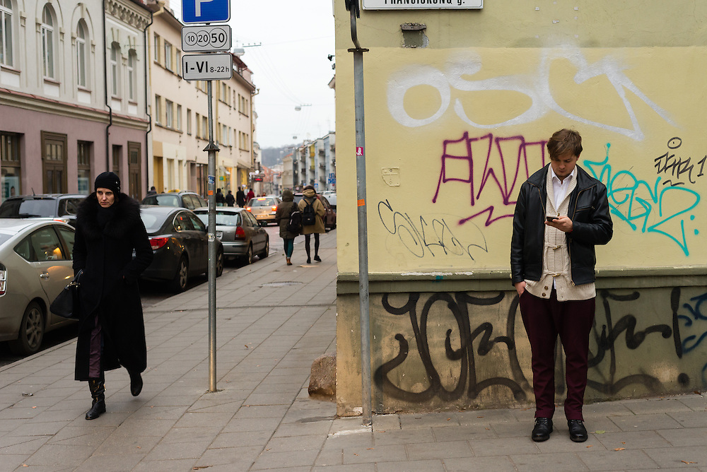 A man stands looking at his phone while a woman smartly dressed strolls by on the streets of Vilnius, Lithuania