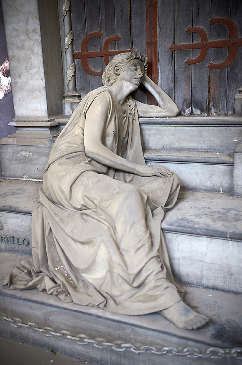 Pictures and image of the stone sculpture of a mouring widow sitting on the steps of the tomb. The Lavarello Family Tomb sculpted by S Saccomanno 1890. Section D no 32, the monumental tombs of the Staglieno Monumental Cemetery, Genoa, Italy .<br /> <br /> Visit our ITALY PHOTO COLLECTION for more   photos of Italy to download or buy as prints https://funkystock.photoshelter.com/gallery-collection/2b-Pictures-Images-of-Italy-Photos-of-Italian-Historic-Landmark-Sites/C0000qxA2zGFjd_k<br /> If you prefer to buy from our ALAMY PHOTO LIBRARY  Collection visit : https://www.alamy.com/portfolio/paul-williams-funkystock/camposanto-di-staglieno-cemetery-genoa.html