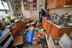 Rachel Cox inspecting flood damage in her kitchen at 37 Oxford street, Nantgarw, in south Wales, where residents are returning to their homes to survey and repair the damage in the aftermath of Storm Dennis.