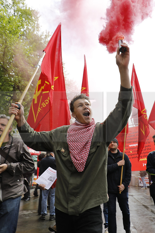 © Licensed to London News Pictures. 01/05/2017. London, UK. A communist campaigner fires a flare as workers and activists take part at a May Day march to Trafalgar Square on May 1, 2017. Photo credit: Tolga Akmen/LNP