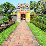 A garden pathin the grounds of the Imperial City in Hue, Vietnam. A self-enclosed and fortified palace, the complex includes the Purple Forbidden City, which was the inner sanctum of the imperial household, as well as temples, courtyards, gardens, and other buildings. Much of the Imperial City was damaged or destroyed during the Vietnam War. It is now designated as a UNESCO World Heritage site.