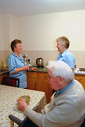 A Care Assistant  makes tea for elderly couple living in new  'extra care' homes;  Bradford,   The self-contained flats have access to 24 hour help; shops and a day centre,