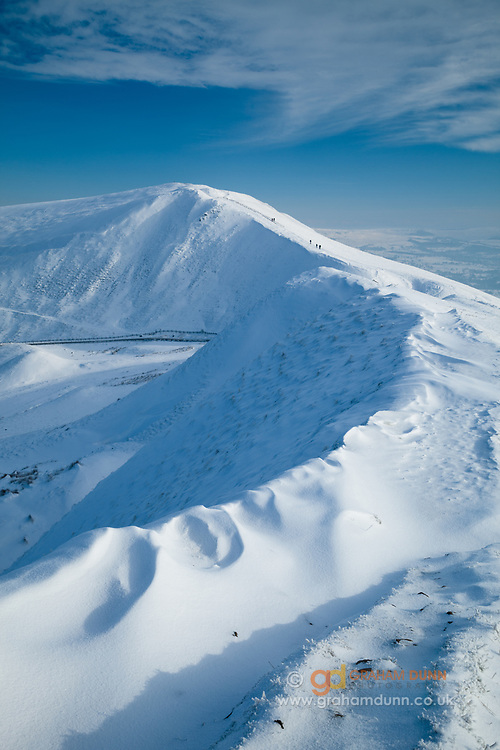 Walkers make their way to Mam Tor's summit, captured from a snow covered Rushup Edge. A winter scene in the Derbyshire Peak District, England, UK.