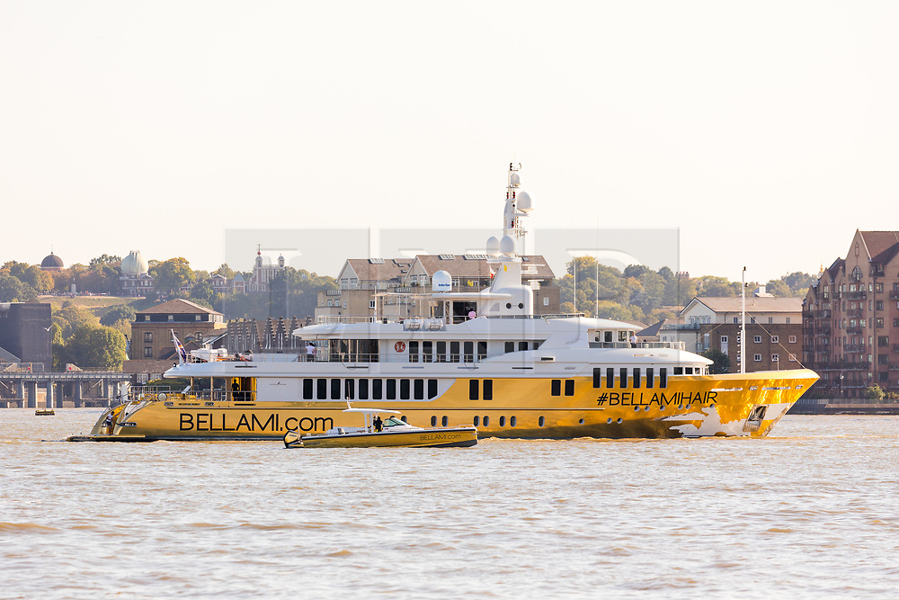 © Licensed to London News Pictures. 17/09/2019. London, UK. Gold wrapped, 175 feet long superyacht, Bellami.com with tender boat arrives in London on the River Thames before mooring in East India Dock. It took 13 days and 600sqm of gold chrome vinyl wrap to cover the superyacht formally known as 'Kinta' at the Port of Viareggio in Italy this year and is the largest chrome yacht wrap done fully in the water and possibly the largest chrome wrap ever. As Bellami.com arrived, it was noticed that some of the chrome wrap was already damaged and missing. Photo credit: Vickie Flores/LNP