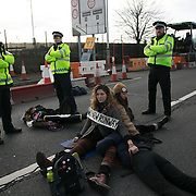 Police officers guard the 5 activists blocking a small slip road to the M4, next to Heathrow whilel they wait for specialist teams to arrive to cut the bike locks and chaines. The two women have locked themselves together with bike locks around their necks and moving them could be extremly harmful. <br /> <br /> November 19 was billed as a day of action by the protest group RisingUp! with activists pledging to arrestable peaceful protetests against the third runway. On the same day residenst around Heathrow gathered to protetst against the airport expansion at a political rally in London. <br /> 15 were arrested on the day, 9 on the slip road to the M4 and charged with 'willfully obstructing the highway'.