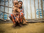 07 NOVEMBER 2014 - SITTWE, RAKHINE, MYANMAR: A Rohingya Muslim girl and her brother in front of their tent in an IDP camp for Rohingya near Sittwe. After sectarian violence devastated Rohingya communities and left hundreds of Rohingya dead in 2012, the government of Myanmar forced more than 140,000 Rohingya Muslims who used to live in and around Sittwe, Myanmar, into squalid Internal Displaced Persons camps. The government says the Rohingya are not Burmese citizens, that they are illegal immigrants from Bangladesh. The Bangladesh government says the Rohingya are Burmese and the Rohingya insist that they have lived in Burma for generations. The camps are about 20 minutes from Sittwe but the Rohingya who live in the camps are not allowed to leave without government permission. They are not allowed to work outside the camps, they are not allowed to go to Sittwe to use the hospital, go to school or do business. The camps have no electricity. Water is delivered through community wells. There are small schools funded by NOGs in the camps and a few private clinics but medical care is costly and not reliable.   PHOTO BY JACK KURTZ