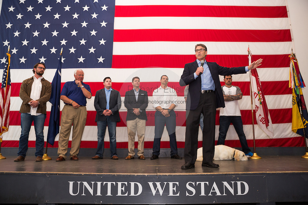Former Texas Governor and GOP presidential hopeful Rick Perry along with a group of military veterans addresses a crowd of supporters during a town hall campaign event aboard the USS Yorktown June 8, 2015 in Mount Pleasant, South Carolina.