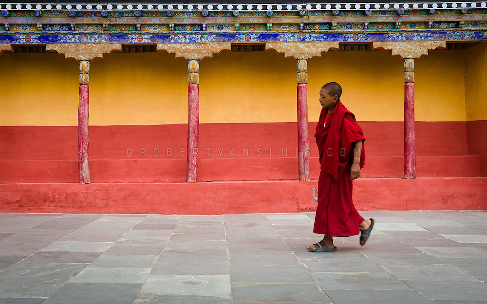 Young monk carrying a pot of tea for morning ceremony at Thiksey Monastery, Ladakh, India