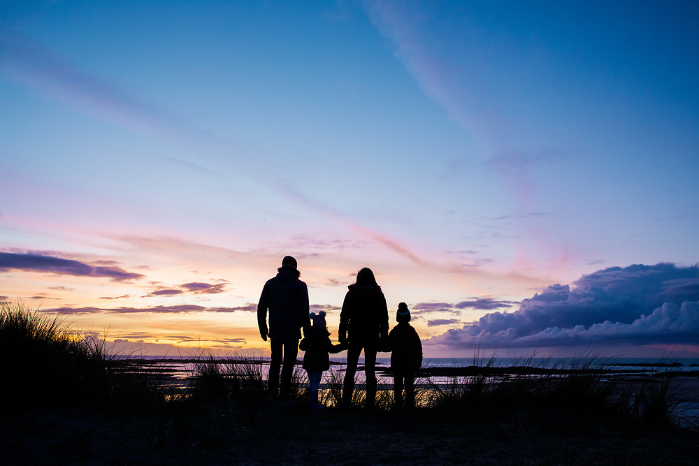 Parents and children standing in the sand dunes looking out over the sea and beach at St Ouen's Bay, with purple orange skies above in Jersey, Channel Islands