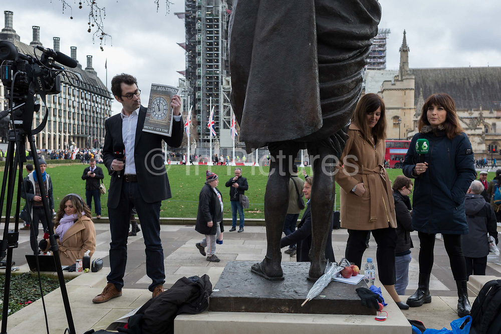 A French TV reporter stands next to the statue of Mahatma Gandhi and holds up the front page of the Times newspaper with the page one picture of Big Ben, on Brexit Day, the day when the UK legally leaves the European Union, in Westminster, on 31st January 2020, in London, England.