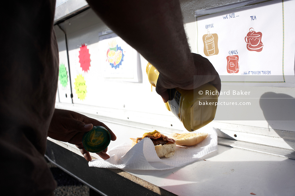 HGV driver pours mustard on to 'bacon buttie' from a mobile burger bar trailer in an overnight lorry park on the A126 in Grays