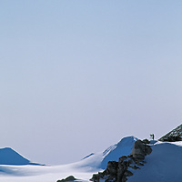 ANTARCTICA. Cinematographer atop outcrop in Queen Maud Mountains, a part of vast Trans-Antarctic Mountains.