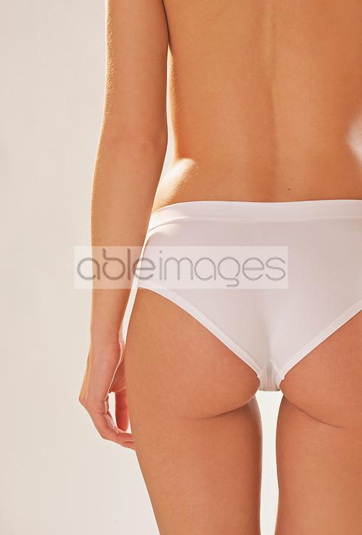 Back view of a woman's body wearing white underwear - headless