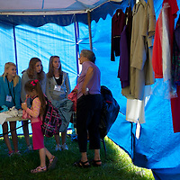 Girls help to distribute clothese at the Remote Area Medical clinic in Wise, Virginia July 20, 2012.  Organizers hope to bring free medical, dental and vision care to more than 3500 uninsured and underinsured people in the rural Virginia area.