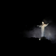 The iconic Cristo Redentor, Christ the Redeemer statue  appears out of the clouds while lit up at night time atop the mountain Corcovado. The Christ statue was voted one of the seven wonders of the modern world in 2007. It was designed by Brazilian Heitor de Silva Costa and was inaugurated in 1931 having taken years to assemble. Rio de Janeiro, Brazil. 23rd July 2010. Photo Tim Clayton..