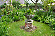 A stone chalice surrounded by borders in the Elizabethan Garden at Stockton Bury Gardens, Leominster, Herefordshire, UK