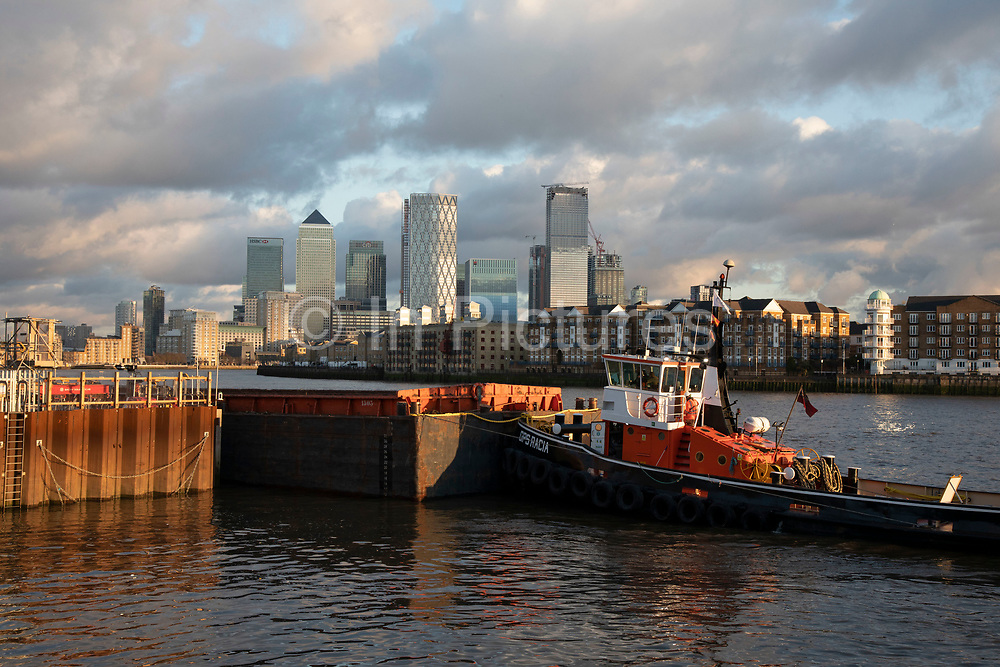 Construction work underway on the Thames Tideway Tunnel or Super Sewer on the River Thames near Wapping, with a tug boat working in the foreground and Canary Wharf and the Docklands Financial District as the background on 18th November 2019 in London, England, United Kingdom. The Thames Tideway Tunnel is an under-construction civil engineering project 25 km tunnel running mostly under the tidal section of the River Thames through central London, which will provide capture, storage and conveyance of almost all the combined raw sewage and rainwater discharges that currently overflow into the river.