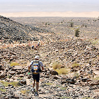 26 March 2007:  Participants run across a rocky oued river bed during the second stage (21.7 miles) of the 22nd Marathon des Sables between Khermou and jebel El Otfal. The Marathon des Sables is a 6 days and 151 miles endurance race with food self sufficiency across the Sahara Desert in Morocco. Each participant must carry his, or her, own backpack containing food, sleeping gear and other material.