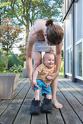 Baby boy stepping to his father shoes with mother assisting him, Munich, Bavaria, Germany