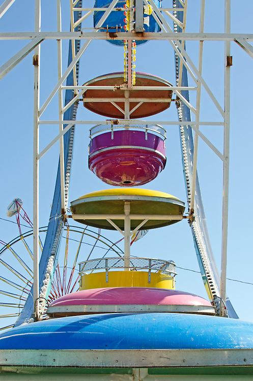 View of a ferris wheel looking up at the gondolas.