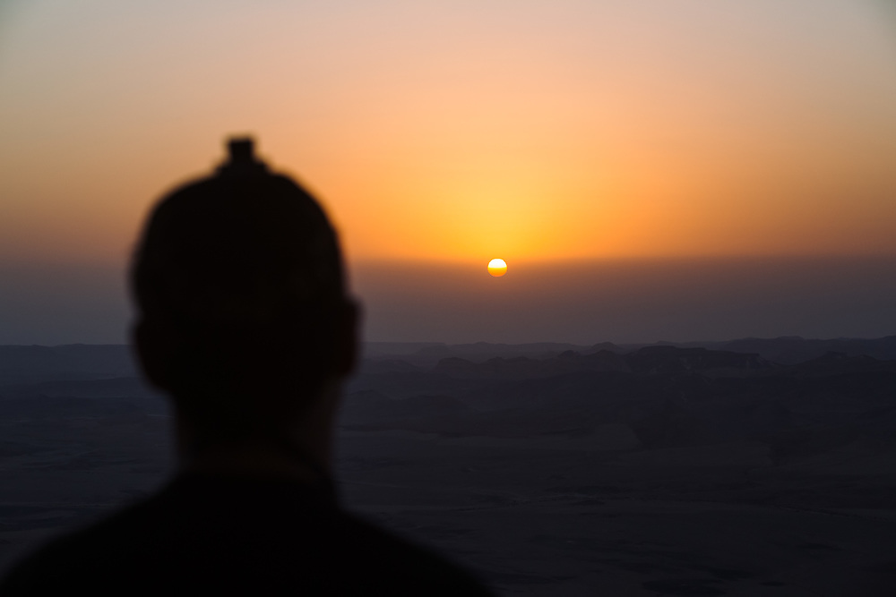 A Jewish man wearing tefillin (or phylacteries), a small black leather box containing scrolls of parchment with verses from the Torah on his forehead, recites a morning prayer as he watches the sunrise over the Ramon Crater (Makhtesh Ramon in Hebrew), the world's largest erosion crater in the Negev desert, southern Israel, on October 18, 2017.