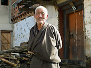 An elderly man wearing a 'gho' the traditional clothing for Bhutanese men outside his farmhouse in Yangthang village, Haa valley, Western Bhutan. The 'gho' is a long robe hoisted to knee length and held in place by a woven cloth belt called a 'kera'. According to tradition, men should carry a small knife called a 'dozum' at the waist.