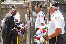 Lt. Gov Osbert Potter lays the memorial wreaths upon the armed service monuments after a roll call of deceased veterans is called out.  St. Thomas Memorial Day Ceremony and Parade.  Franklin D. Roosevelt Veterans Park.  St. Thomas, USVI.  30 May 2016.  © Aisha-Zakiya Boyd
