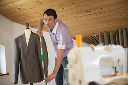 Male dressmaker measuring jacket on dressmaker's model, Bavaria, Germany