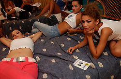 Women  relax after getting their hair and makeup done hours  before a fashion show in which they  will model at the Aguasal beach club .  The beach club hosts several fashion shows each year and holds its own beauty pageant.  Fashion and looking good are top priorities in Venezuela, where there is a general culture of beauty.  It is a culture that permeates all walks of life and covers the country like a blanket. Girls enter beauty pageants as toddlers and young women and men get plastic surgery as teens.  Venezuela is a country where thongs and short skirts are the norm, cleavage awaits around every corner and metrosexual men abound.