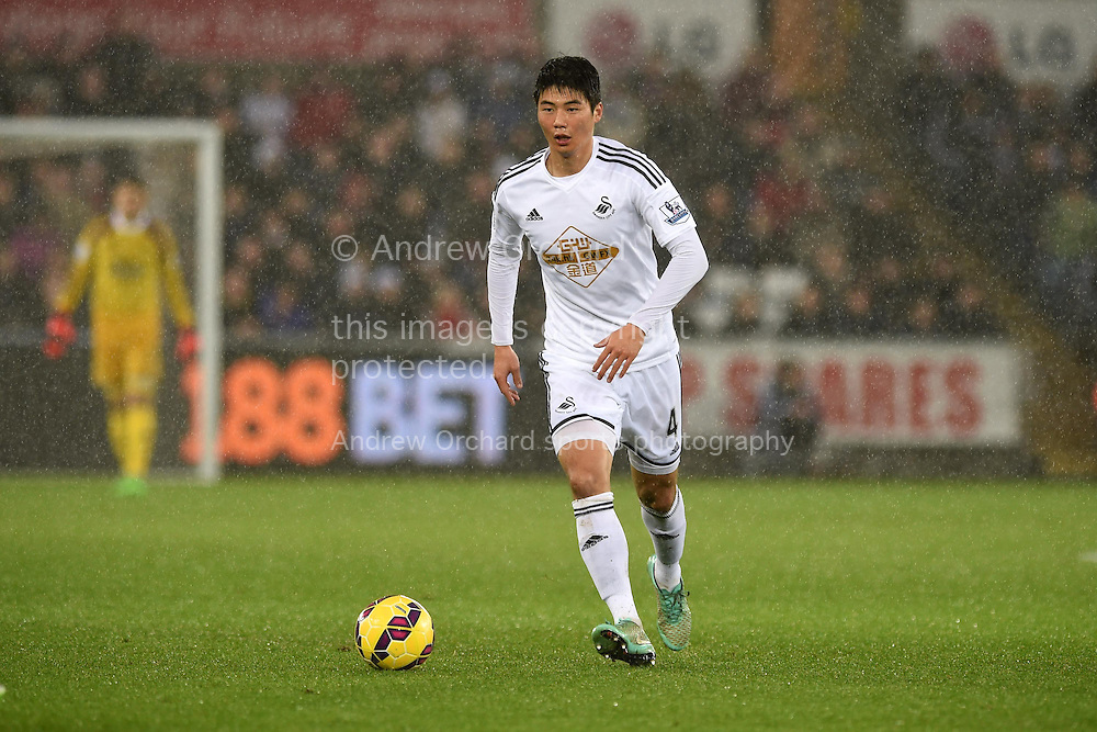 Ki Sung-Yueng of Swansea city makes a break.Barclays Premier league match, Swansea city v Aston Villa at the Liberty stadium in Swansea, South Wales on Boxing Day, Friday 26th December 2014<br /> pic by Andrew Orchard, Andrew Orchard sports photography.