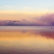 The combination of early morning light and a lingering fog create a beautiful display of colors and reflections on the Hudson River at Tarrytown, NY.