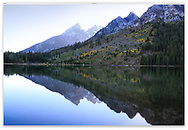 The high peaks perfectly reflected in Jenny Lake after an autumn rain storm, Grand Teton National Park, Wyoming, USA
