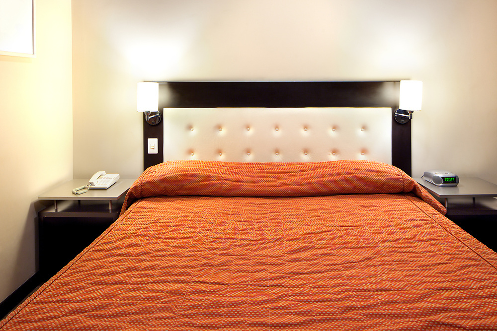 Frontal view of a double bed with red bedspread.
