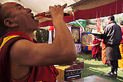 "Sitting in lawn chairs under a tent with other guests of honor, a lama takes a swig of Pepsi during the electricity celebration. Chato Namgay (in red robe) has just lit the ritual butter lamps on an altar below the transformer on the power pole. Above a photo of the king, a sign reads: ""Release of Power Supply to Rural Households Under Wangdi Phodrang Dzon Khag to Commemorate Coronation Silver Jubilee Celebration of His Majesty, King Jigme Singye Wangchuk."" Hungry Planet: What the World Eats (p. 43). The Namgay family living in the remote mountain village of Shingkhey, Bhutan, is one of the thirty families featured, with a weeks' worth of food, in the book Hungry Planet: What the World Eats."