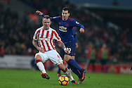 Henrikh Mkhitaryan of Manchester Utd ® challenges Glenn Whelan of Stoke city. Premier league match, Stoke City v Manchester Utd at the Bet365 Stadium in Stoke on Trent, Staffs on Saturday 21st January 2017.<br /> pic by Andrew Orchard, Andrew Orchard sports photography.