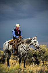 Hamer Idaho rancher, Lance Moss astride his grey despite the approaching storm.