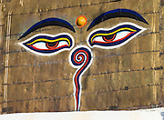 """Buddha Eyes gaze from one side of Swayambhunath, the """"Monkey Temple"""" in Kathmandu, Nepal, Asia. On most every stupa (Buddhist shrine) in Nepal, giant Buddha Eyes (or Wisdom Eyes) stare from four sides of the upper cube. These four directions symbolize the omniscience (all-seeing) of a Buddha. The third eye (above and between the other two eyes) also symbolizes the all-seeing wisdom of the Buddha. The curled symbol (shaped like a question mark) in place of a nose is the Nepali character for the number 1, which symbolizes unity of all things."""